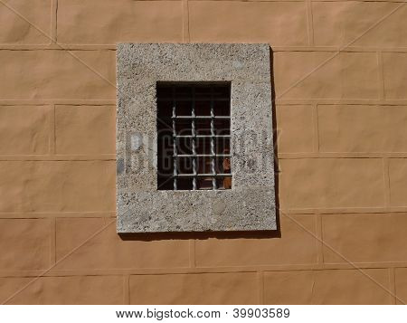 small window on yellow wall