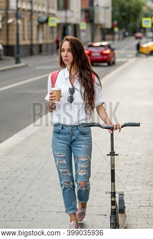 Beautiful Woman Walks Around City With Scooter, Walk In Summer After Work, Breakfast And Lunch In He