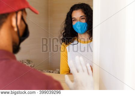 Mixed race woman wearing a face mask greeting delivery man at door. self isolation at home during covid 19 coronavirus pandemic.
