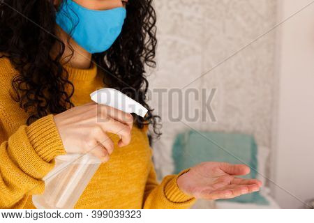Mixed race woman wearing a face mask disinfecting hands with spray. portrait of mixed race woman with long hair wearing face mask. self isolation at home during covid 19 coronavirus pandemic.