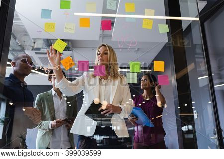 Diverse business people brainstorming by glass board in office. modern creative business professionals meeting workplace.