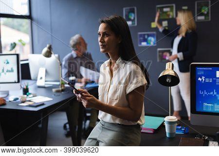 Mixed race businesswoman sitting on desk using digital tablet in creative office. modern office business teamwork technology.