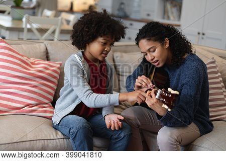 Mixed race woman and daughter sitting on couch. playing a guitar. self isolation quality family time at home together during coronavirus covid 19 pandemic.