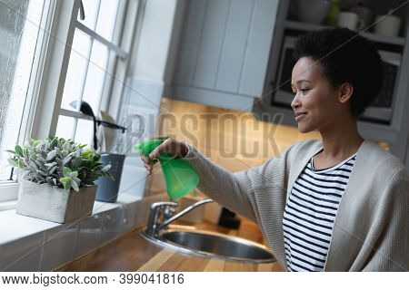 Mixed race woman watering plants in kitchen. self isolation quality family time at home together during coronavirus covid 19 pandemic.