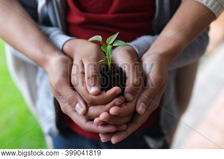 Mixed race woman and daughter holding a plant. self isolation quality family time at home together during coronavirus covid 19 pandemic.