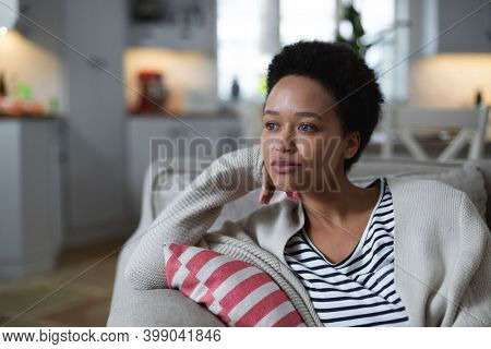 Mixed race woman sitting on couch looking sad. self isolation quality family time at home together during coronavirus covid 19 pandemic.
