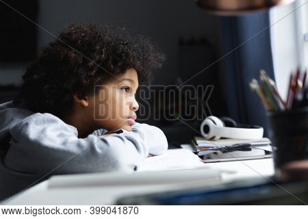 Mixed race girl lying on a desk. looking through a window. self isolation quality family time at home together during coronavirus covid 19 pandemic.