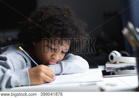Mixed race girl lying on a desk drawing in notebook. self isolation quality family time at home together during coronavirus covid 19 pandemic.