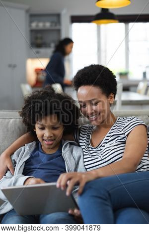Mixed race woman and daughter sitting on couch. using digital tablet. self isolation quality family time at home together during coronavirus covid 19 pandemic.