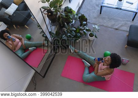 Overhead view of african american woman sitting on exercise mat drinling water. self isolation fitness at home during coronavirus covid 19 pandemic.