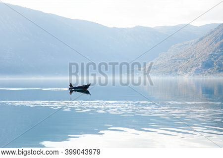 Autumn Landscape With Boat And Fisherman. Fishing In Foggy Morning Lake. Amazing Nature With Mountai