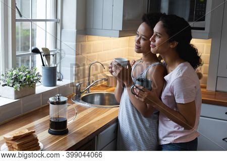 Smiling mixed race lesbian couple drinking coffee and embracing in kitchen. self isolation quality time at home together during coronavirus covid 19 pandemic.