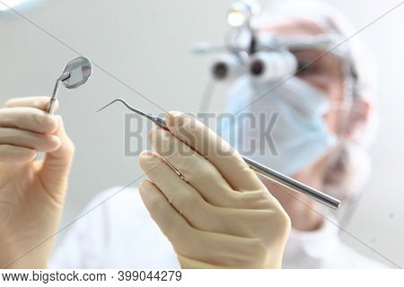 A Doctor Wearing Binocular Glasses Holds A Dental Mirror And Tweezers In His Hand. The Face Is Out O