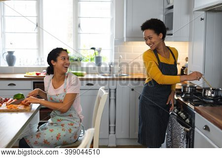 Mixed race lesbian couple preparing food in kitchen. self isolation quality family time at home together during coronavirus covid 19 pandemic.