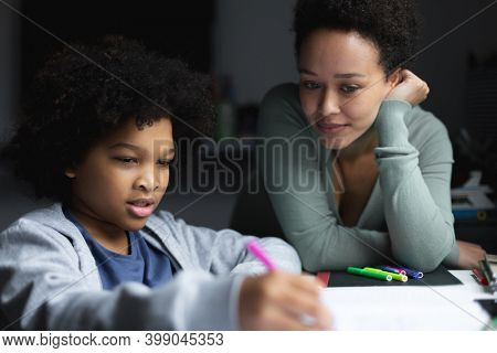 Mixed race woman watching daughter drawing in notebook. self isolation quality family time at home together during coronavirus covid 19 pandemic.