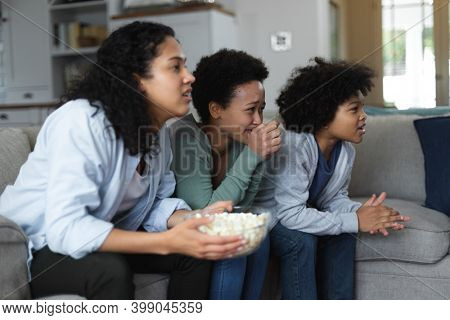 Mixed race lesbian couple and daughter sitting on couch watching tv and eating popcorn. self isolation quality family time at home together during coronavirus covid 19 pandemic.