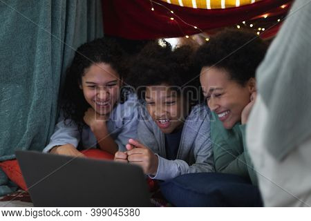 Mixed race lesbian couple and daughter lying in blanket fort using laptop. self isolation quality family time at home together during coronavirus covid 19 pandemic.