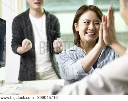 Team Of Three Asian Business People Giving Hi-five Celebrating Achievement And Success In Office