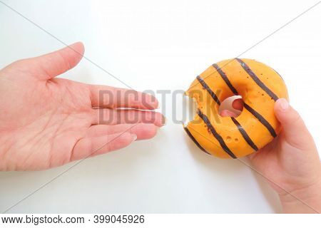 Child Hand Holds A Bitten Orange Chocolate Donut Holds Out His Mom Hands On A White Background