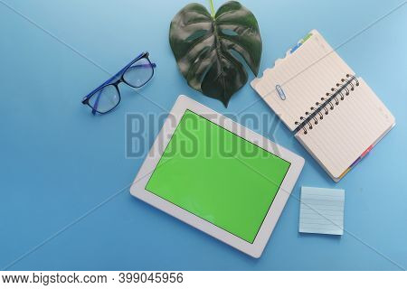 Top View Of Digital Tablet With Office Suppliers On Blue Background