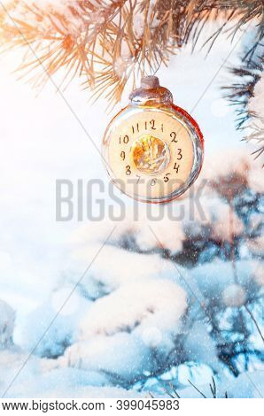 Christmas background. Christmas card. Christmas and New Year background - Christmas toy in the form of clock showing the New Year Eve, on snowy fir tree branch, Christmas background