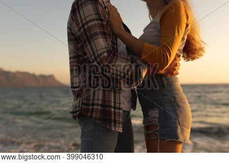 Mid section of a Caucasian couple standing on a promenade by the sea at sunset, facing each other and embracing. Romantic seaside holiday couple