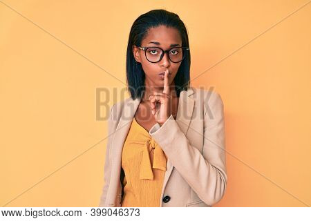 Young african american woman wearing business clothes asking to be quiet with finger on lips. silence and secret concept.