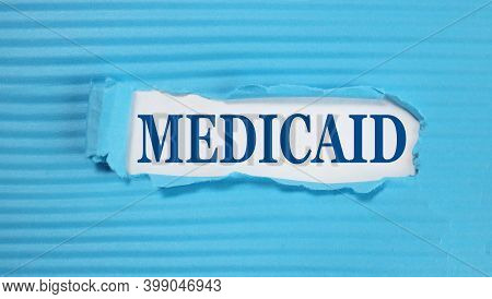 Medicaid. Text On White Paper On Torn Blue Paper Background