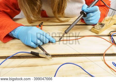 The Woman Solders The Wires With A Soldering Iron. Female Hands In Rubber Gloves Hold A Soldering Ir