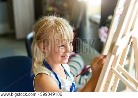 Cute Blond Smiling Caucasian Kid Painting On Wooden Easel In Class Workshop Lesson At Art Studio. Li
