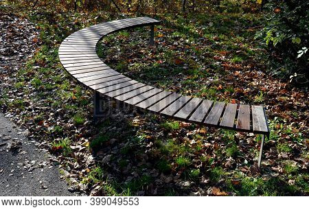 Circular Bench In The Shape Of An Arch With Wood Paneling With Brown Wooden Planks. Yellow Leaves Li
