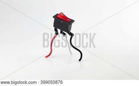 Power up, start up concept image. Red switch  standing up with red black and white cable legs. Switch in