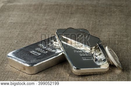 Silver Bullion. Cast And Minted Silver Bars And Coins Against The Background Of The Texture Of Coars