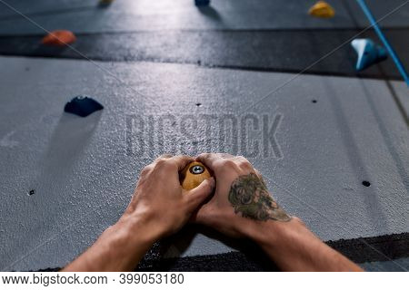 Close Up Of Hands Of Man Climbing Up On Rock Wall In Gym. Bouldering Training Concept. Focus On Hand