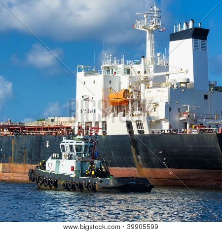 Small tugboat guiding a huge cargo ship in the bay of Havana