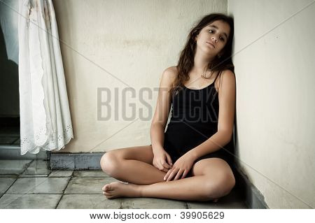 Grunge image of a sad and lonely latin  girl sitting in the corner of a dirty house