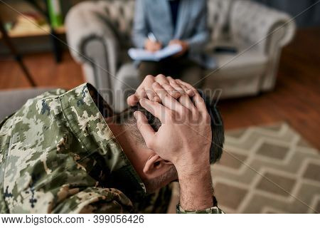 Close Up Of Military Man Holding His Head In Pain And Depression During Therapy Session With Psychol