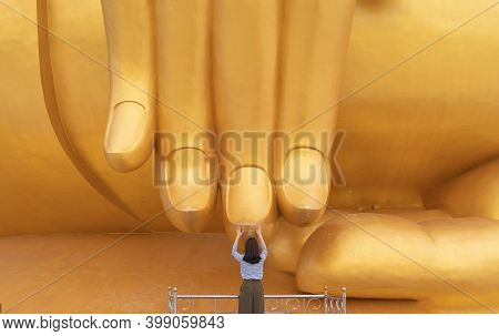 Asian Woman Pay Respect At The Finger Of Giant Golden Buddha In Wat Muang In Ang Thong District Near