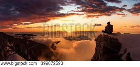 Adventurous Man Is Sitting On The Edge Of A Cliff And Enjoying The Beautiful Mountain Scenery. Adven