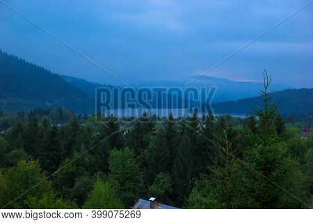 Landscape Of Lake Bicaz With Ceahlau Massif On The Background. Beautiful Evening View Of Lakul Izvor