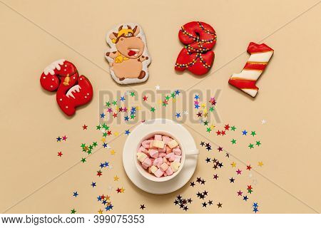 Numbers 2021 Made From Gingerbread Cookies In Multi-colored Glaze On A Beige Background. A Cup With
