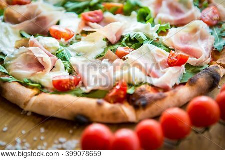 Pizza With Cherry Tomatoes, Prosciutto And Ruccola. Shallow Dof