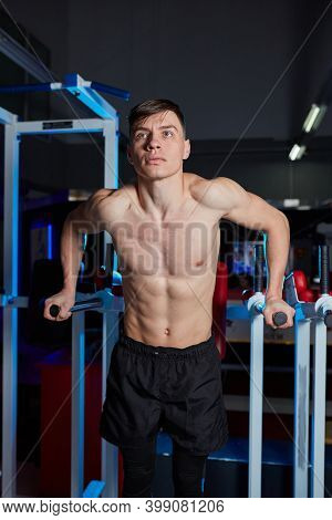 Fitness, Sport And People Concept - Young Man Doing Triceps Exercise Diving On Uneven Bars In The Gy