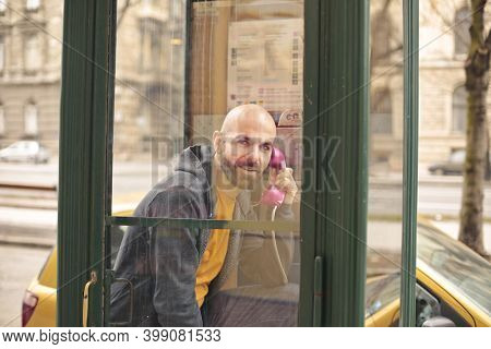 man speaks in a telephone booth