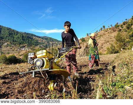 Mandi, Himachal Pradesh, India 11 28 2020:  A Young Indian Boy Driving Mini Tractor For Wheat Cultiv