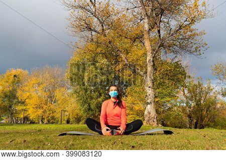 Sporty Dressed Woman Doing Stretching In The Lotus Flower Position On A Mat In The Park Wearing A Ma
