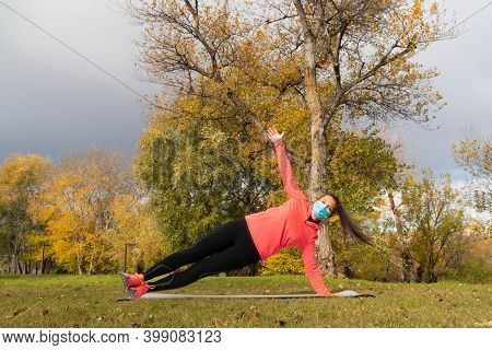 Sporty Dressed Woman Doing The Side Plank On A Mat In The Park Wearing A Mask To Protect Herself Fro