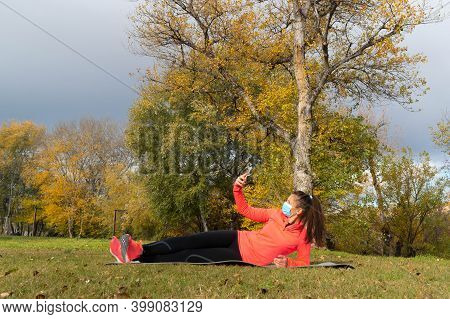 Sporty Dressed Woman Lying On A Mat In The Park Wearing A Mask To Protect Herself From The Coronavir