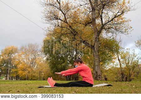 Sporty Dressed Woman Stretches Trying To Touch Her Toes On A Mat In The Park Wearing A Mask To Prote