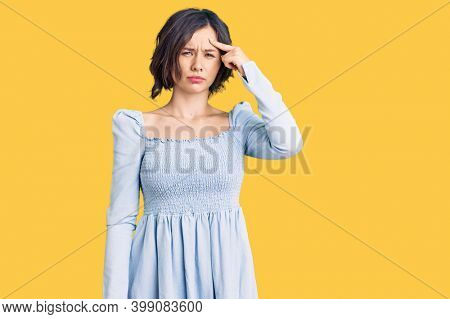 Young beautiful girl wearing casual clothes pointing unhappy to pimple on forehead, ugly infection of blackhead. acne and skin problem
